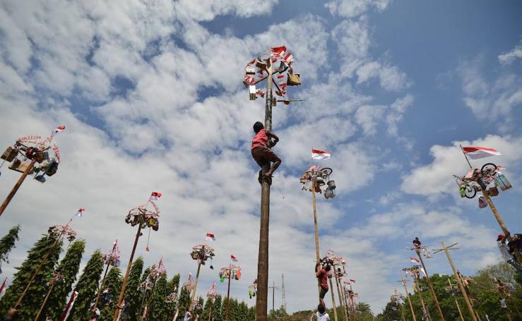 Fotos del Panjat Pinang de Indonesia, la tradición de escalar un palo engrasado