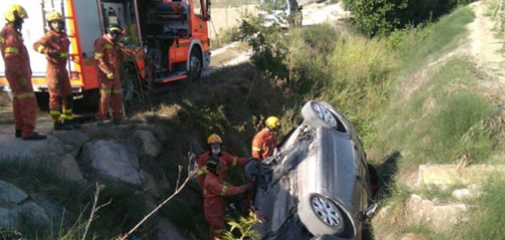 Los bomberos rescatan a dos heridos atrapados tras volcar un coche en Ontinyent
