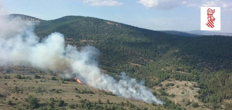 Cinco medios aéreos y 60 bomberos trabajan en la extinción de un incendio en una zona de matorral cerca del Penyagolosa