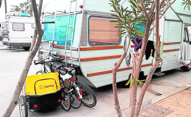 Caravanas y bicis. Una de las autocaravanas en la Malvarrosa, ayer.