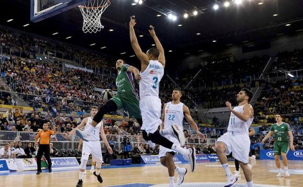 El base de Unicaja, Ray McCallum, entra a canasta defendido por Anthony Randolph del Real Madrid./EFE