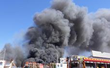 Medios terrestres y aéreos trabajan en el incendio de un almacén de reciclaje de Elche