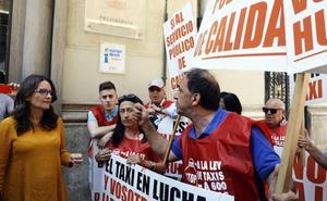 Los taxistas abordan a Mónica Oltra tras el pleno del Consell para mostrar su enfado por la ley del taxis
