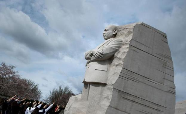 Un grupo de personas señala la estatua en honor a Martin Luther King en Washington.