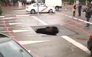 Un coche se cae por un socavón en plena calle