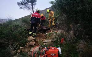 Los bomberos desguazan y retiran los restos de un coche que llevaba años abandonado en el parque natural del Montgó