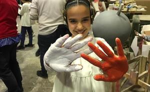 Sara Larrazábal y su corte pintan una falla con sus manos para decir 'stop' a las guerras