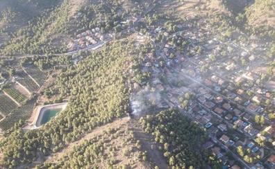 El esfuerzo de los bomberos para evitar que un incendio forestal afecte a la urbanización San Miguel de Náquera