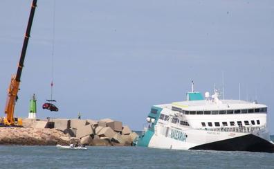 Una gran grúa saca desde tierra los coches del ferry encallado en Dénia