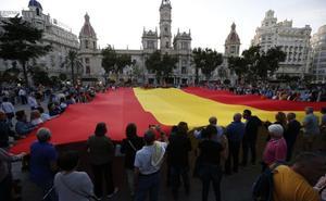 Despliegan una bandera de España en una manifestación en la plaza del Ayuntamiento de Valencia