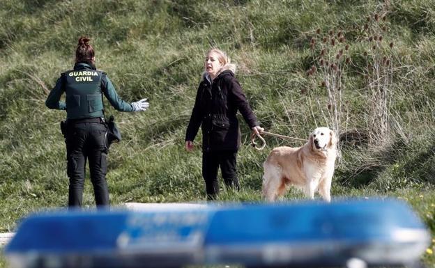Un efectivo de la Guardia Civil conversa con una persona que acompañada de su perro se ha alejado demasiado de su vivienda siendo advertida para que regrese a su vivienda.