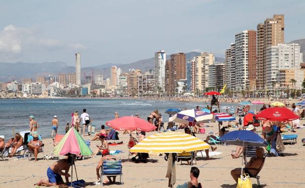 Decenas de personas disfrutan de un soleado día de playa en Benidorm./ Tino Calvo