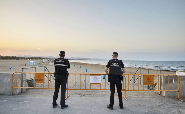 Dos agentes de la Policía Local de Valencia frente a una playa.  / IVÁN ARLANDIS